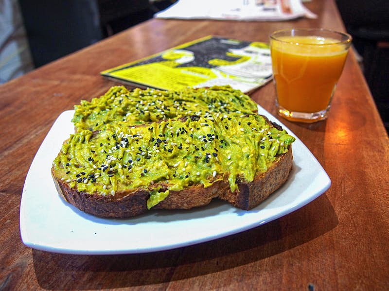 A toast spread with avocado and topped with small seeds, with a small cup of orange juice in the background. Santiago, Chile.