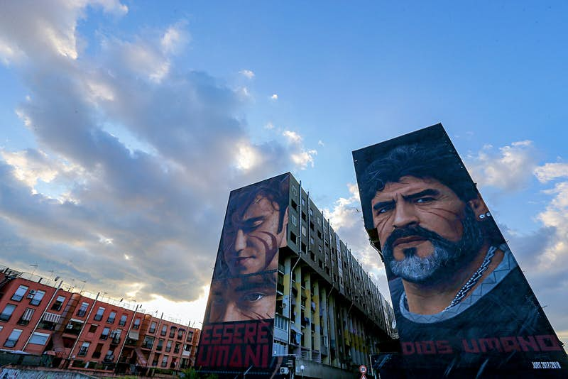 The side of an apartment building is decorated with two huge murals, one of the footballer Maradona's face and the other of a boy's face, both with red face paint on their cheeks