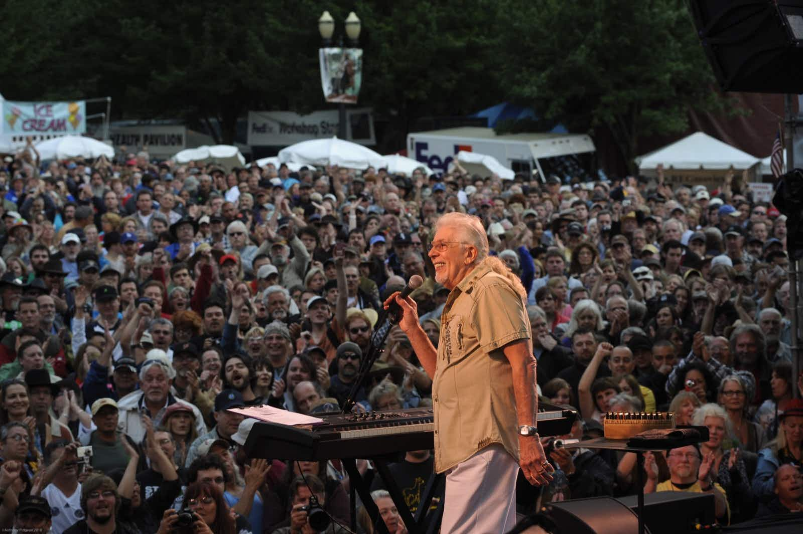 A huge crowd of concertgoers are seen behind a white haired man playing on stage