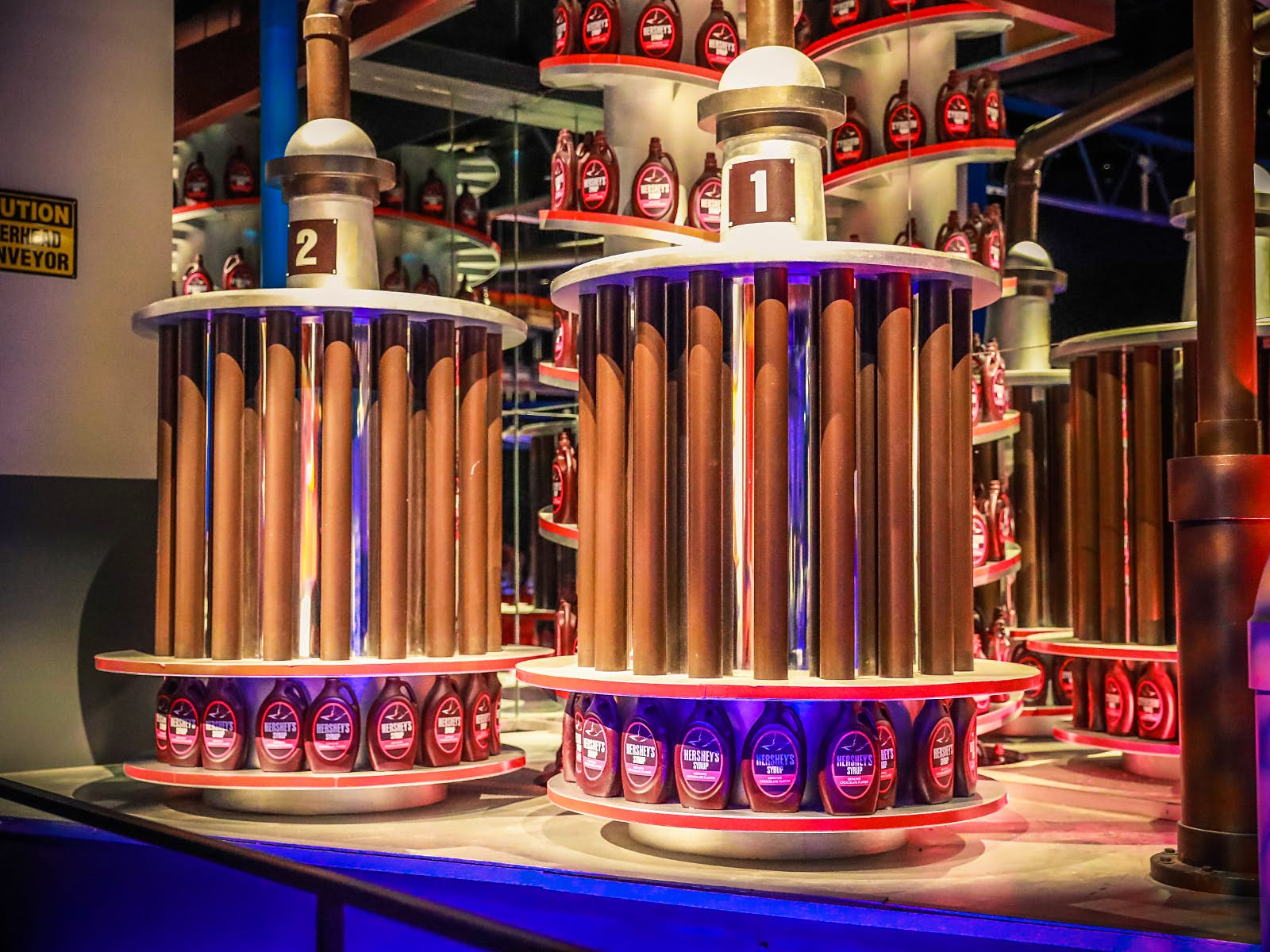 Disney alternatives - Inside Hershey's Chocolate World. Bottles of chocolate sauce line the walls and displays