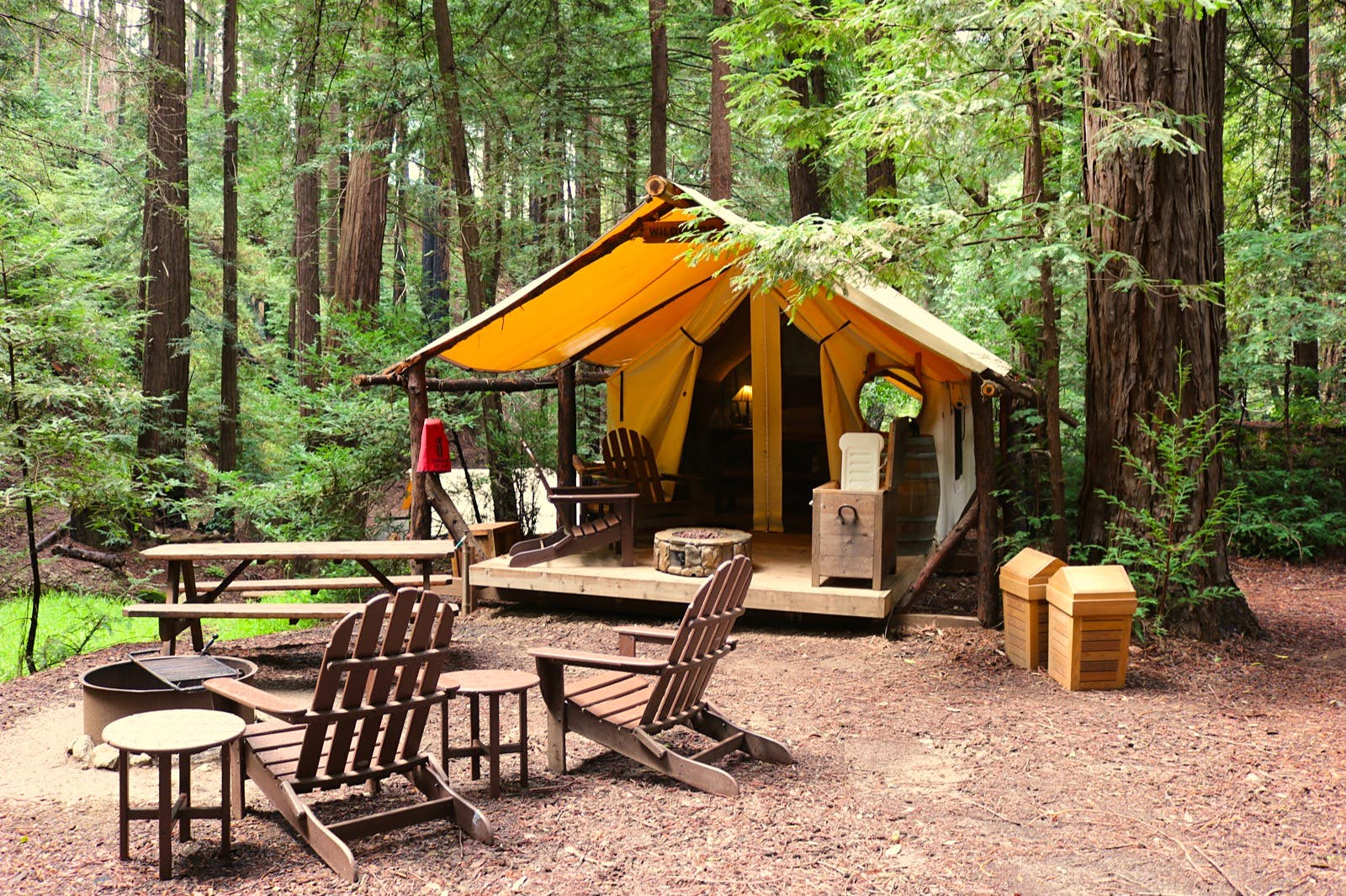 Adirondack chairs surround a fire pit with a safari-style tent in the background