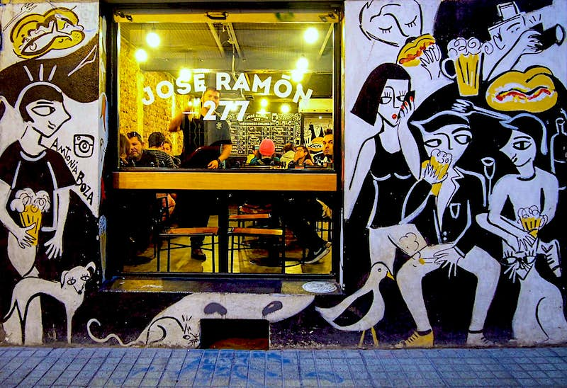 The exterior of restaurant Jose Ramon; one window is surrounded by a wall of black and white murals of people eating food. Santiago, Chile.