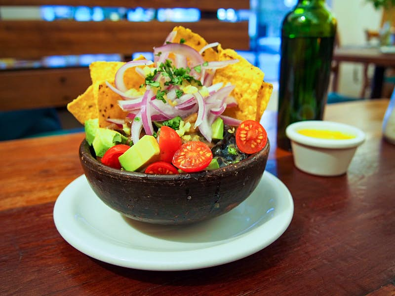 A stone bowl sits full of vegetarian ceviche containing avocado, tomatoes, kelp, onion and corn chips at El Huerto. Santiago, Chile.
