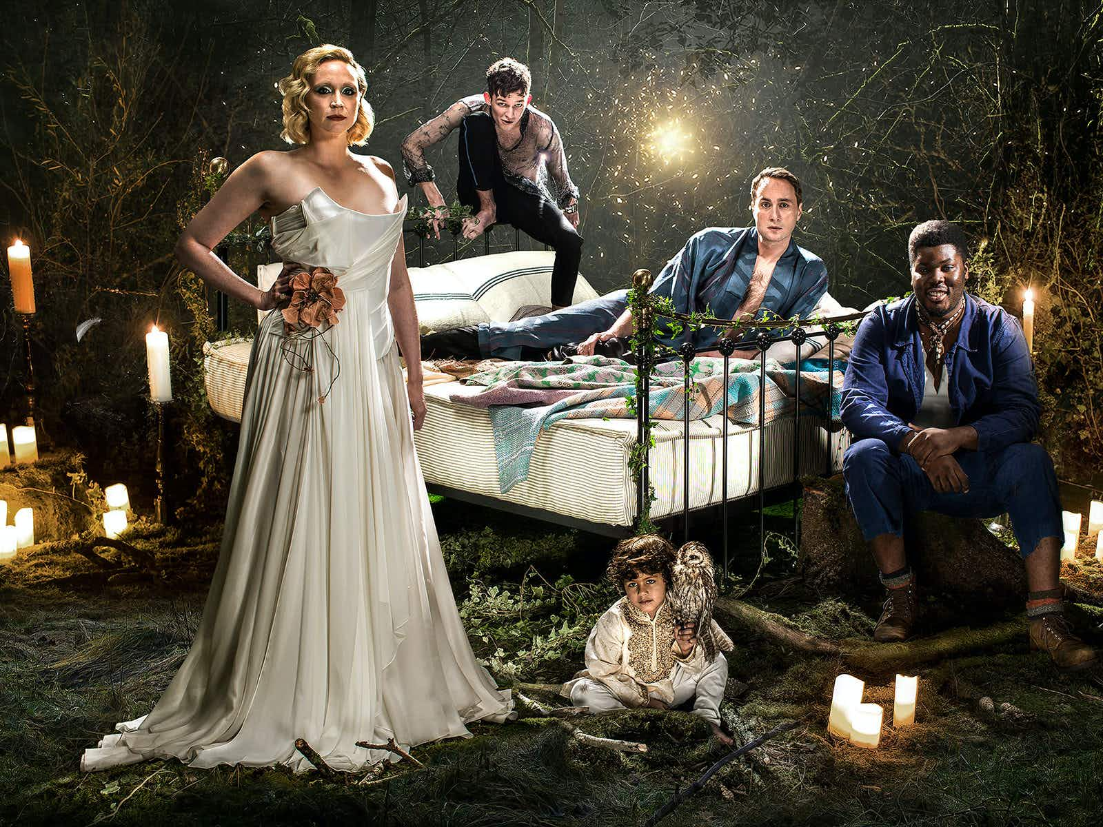 Celebrities West End Braodway - Gwendoline Christie leads the cast of A Midsummer Night's Dream at the Bridge Theatre, London. Gwendoline stands in front of the other cast members, posed around a wrought iron bed, in a floor-length, white silk gown © Perou