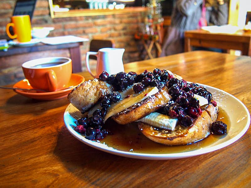 A plate with french toast topped with bananas and blueberries, with a cup of coffee in the background. Santiago, Chile.