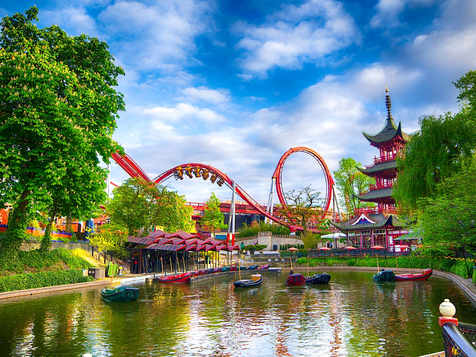 Disney alternatives - Colourful Tivoli Gardens in Copenhagen. A red rollercoaster twists over the park's lake which has small green and red boats floating on it