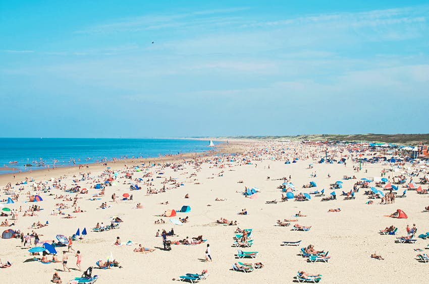 Features - High Angle View Of People At Beach Against Sky
