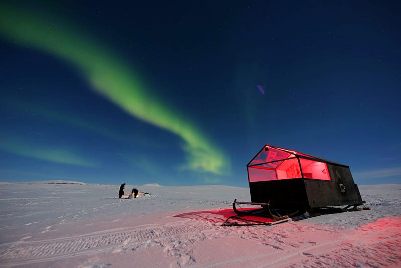 A small hut with a clear roof stands on large skis in the middle of a snowy, bare landscape with the Northern Lights in the sky and two people standing the background.