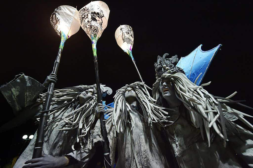 Three performers with grey robes and hair and blue wings hold lanterns during the night time parade.