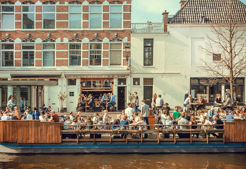 Features - Many people eating and talking on riverboat cafe on the canal in a sunny day