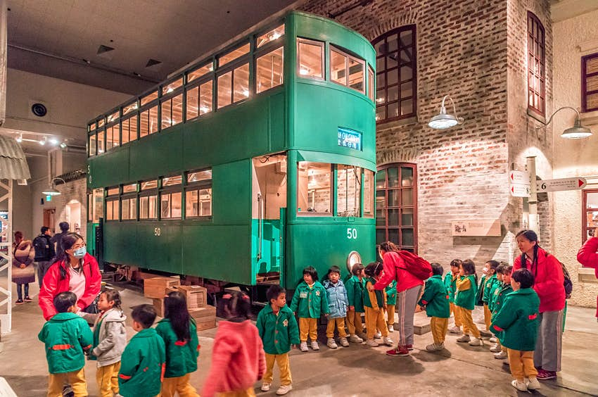 Schoolchildren examine an old tram carriage in the Hong Kong Museum of History