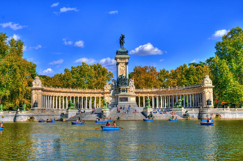 People in boats by the Monument to Alfonso XII in Madrid's Parque del Buen Retiro