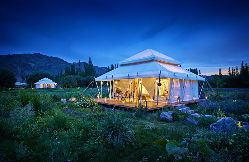 A square white tent with two-tired pyramidal roof glows with soft light in the dusk with the mountains of Ladakh in the background; the tent sits amongst lush vegetation, another similar tent is in the distance