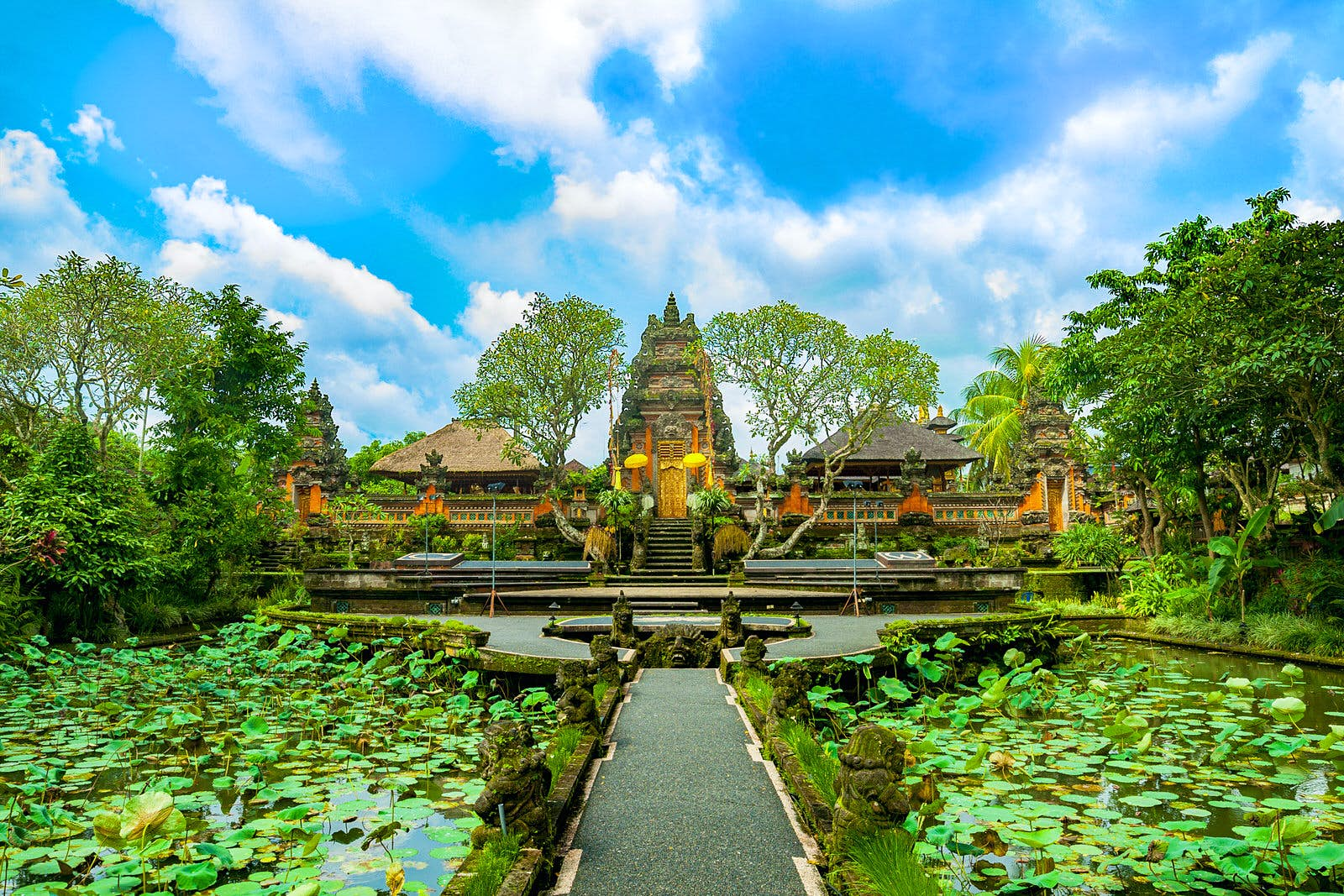 A paved path leads across a lotus covered pond in front of the towering temple of Pura Taman Saraswati in Ubud, Bali; on either side of the carved stone tower are two pyramid shaped roofs over open-air areas