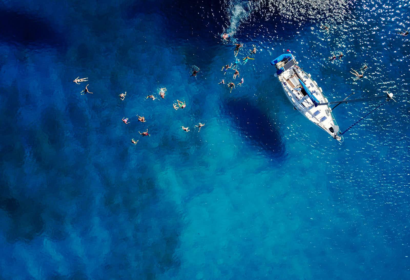 Aerial of a group of people swimming in blue water near a yacht ©Dusan Petkovic/Shutterstock