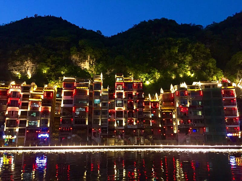Evening lights reflected in the Wuyang River in Zhenyuan © Megan Eaves / Lonely Planet