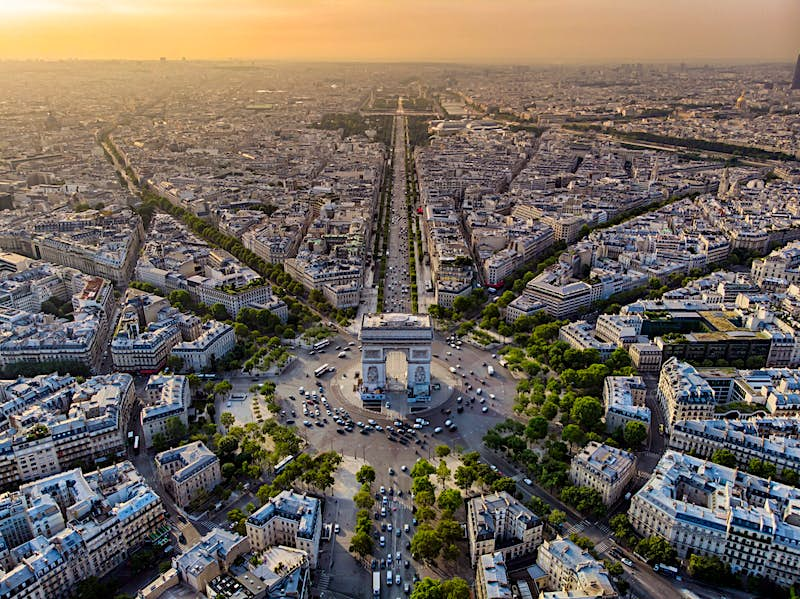 An aerial shot of the Arc de Triomphe, which stands in the centre of a roundabout and has roads stretching away in 12 different directions