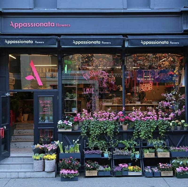 Appassionata Flowers shop front. There are rows of coloured flowers stacked in front of the big windows and black shop front