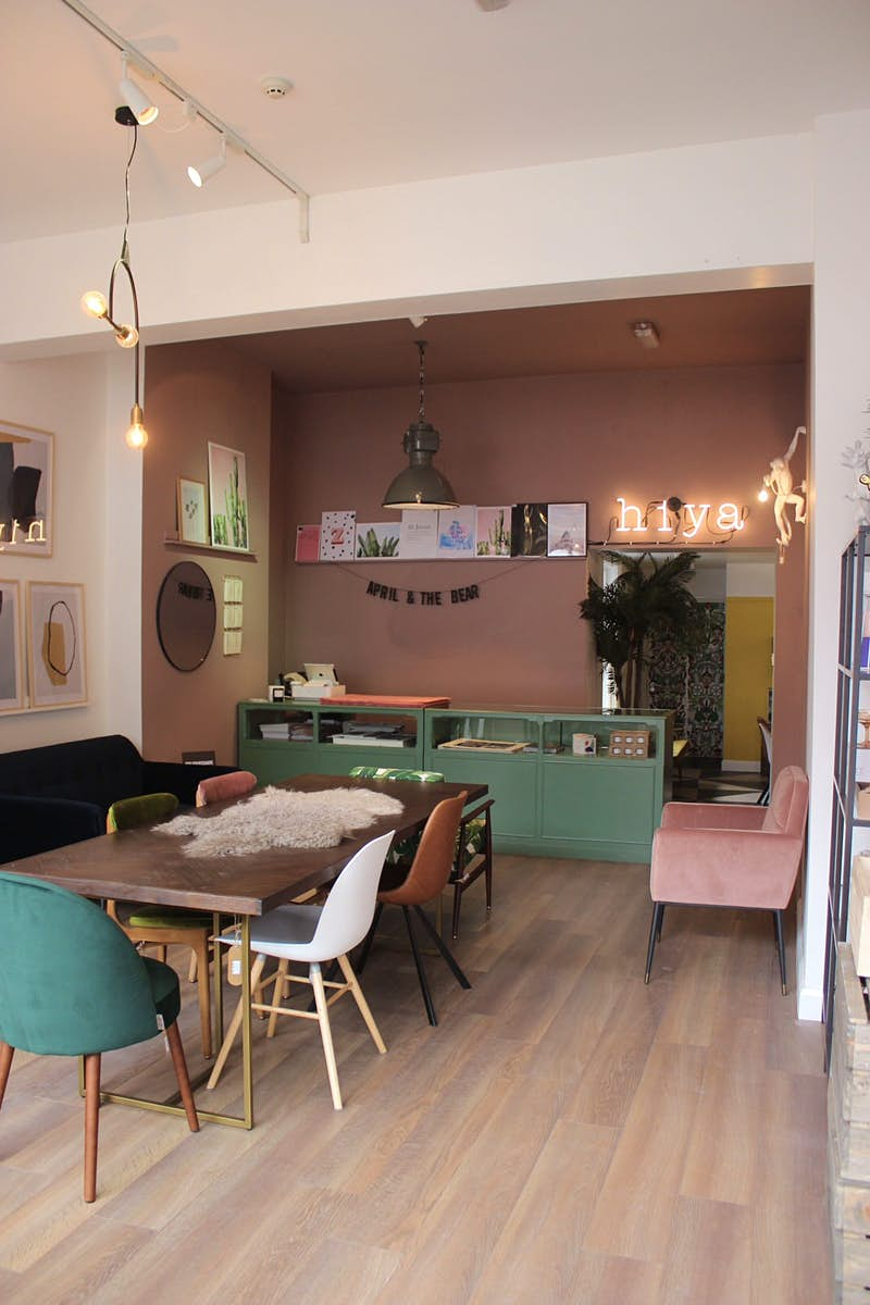 Dublin independent shops - the interior of April and the Bear independent shop with a long dark wood table in the middle surrounded by multicoloured chairs. There is a neon sign that says 'hiya' on the light-pink walls as well as other artwork and mirrors