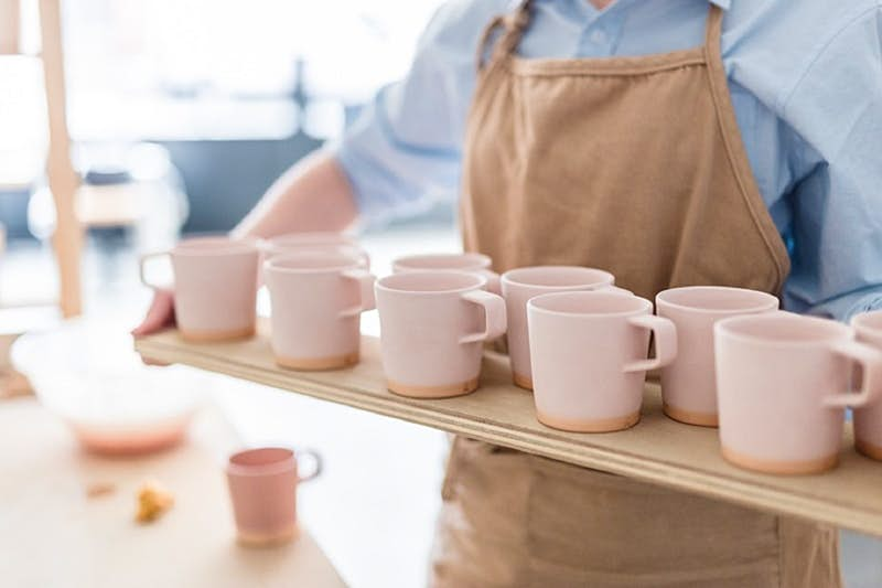 Dublin independent shops - a long wooden tray of light-pink clay mugs being carried by someone in a blue shirt and brown apron whose head's been cropped out