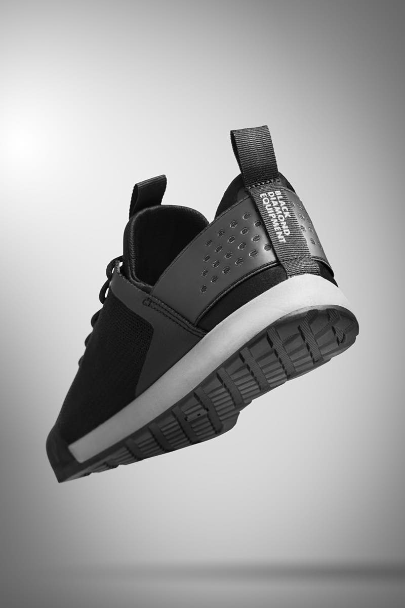 the rear of a black sneaker with rubber soles and sturdy heel compartment