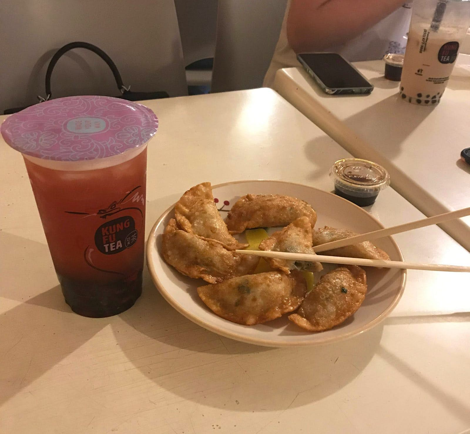 A strawberry green bubble tea from Kung Fu Tea, accompanied by some fried chicken dumplings.