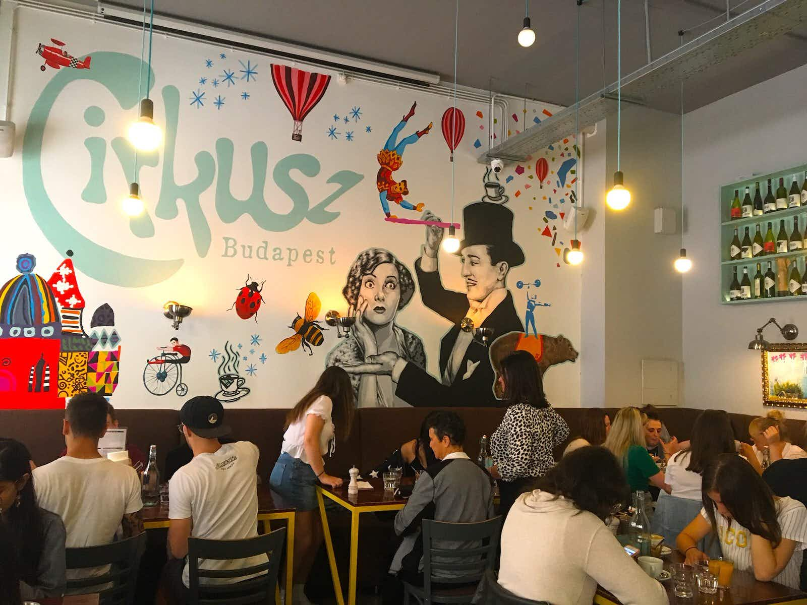 Dinners cram into a high-ceilinged cafe with light bulbs hanging from long wires; the back wall is covered in a vibrant mural of balloons, flying trapeez artists, planes and lady birds