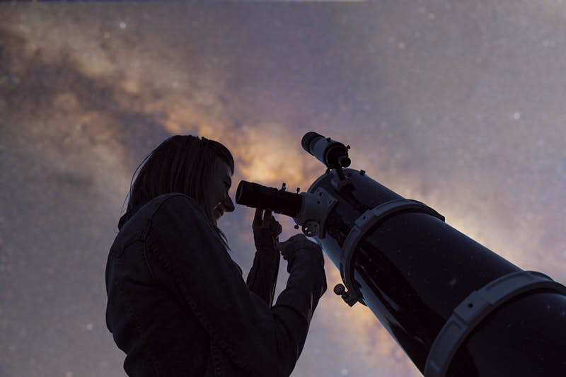 Silhouette of a girl and telescope with de-focused Milky Way stars.