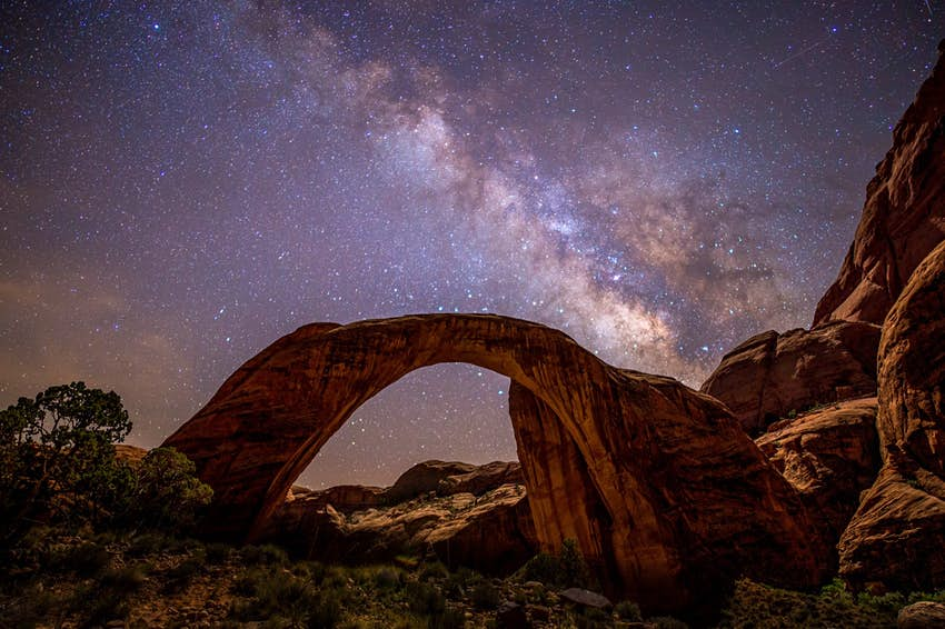 The Milky Way is seen in a dark sky above the stone arch of Rainbow Bridge National Monument