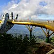 A single giant concrete hand can be seen holding the golden walkway of the bridge, as several people enjoy the view of jungle and hills that stretches for miles