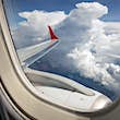 Thick clouds outside an airplane window; what causes airplane turbulence