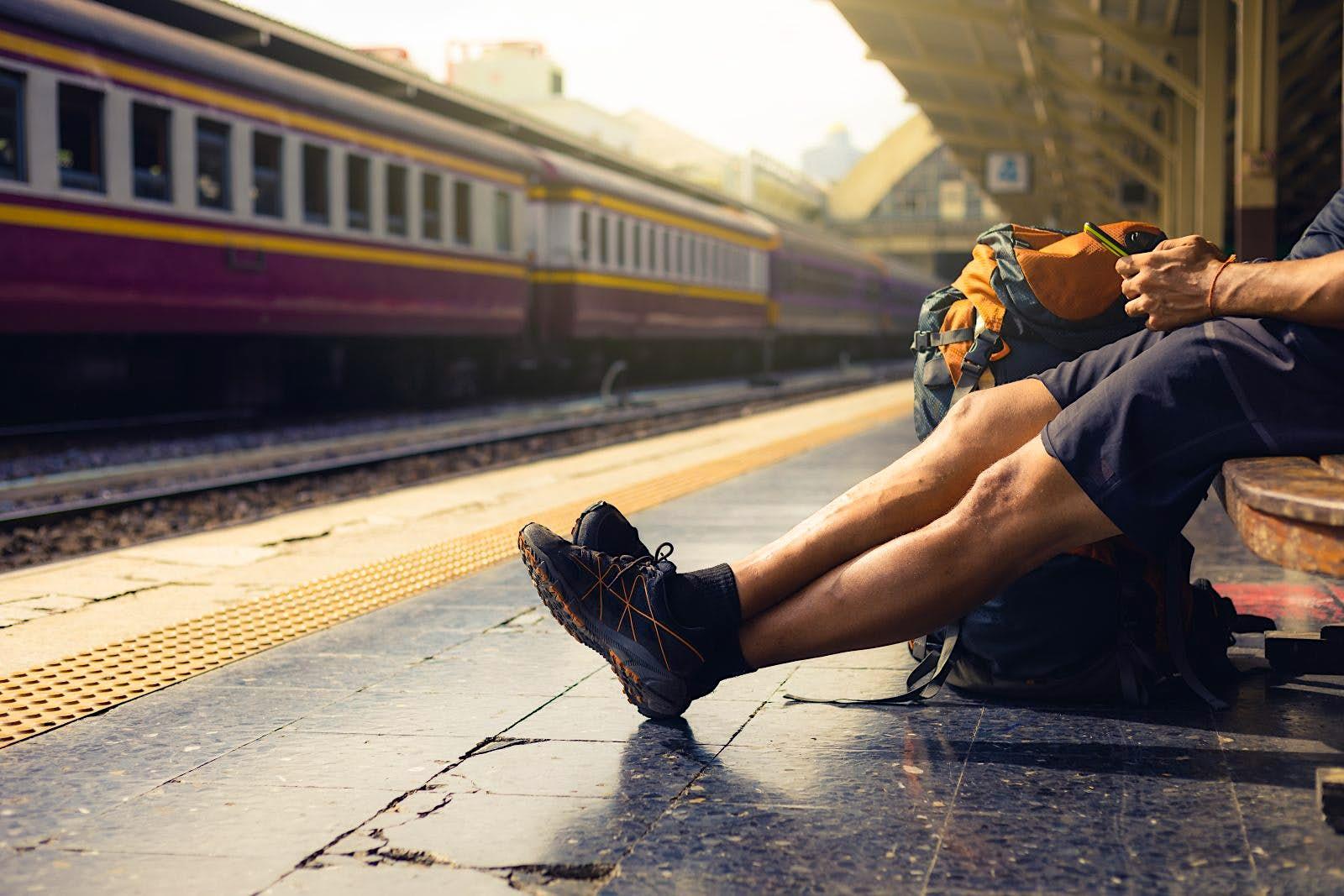 Ein männlicher Reisender spielt auf seinem Telefon, während er auf einer Bank in einem Bahnhof sitzt