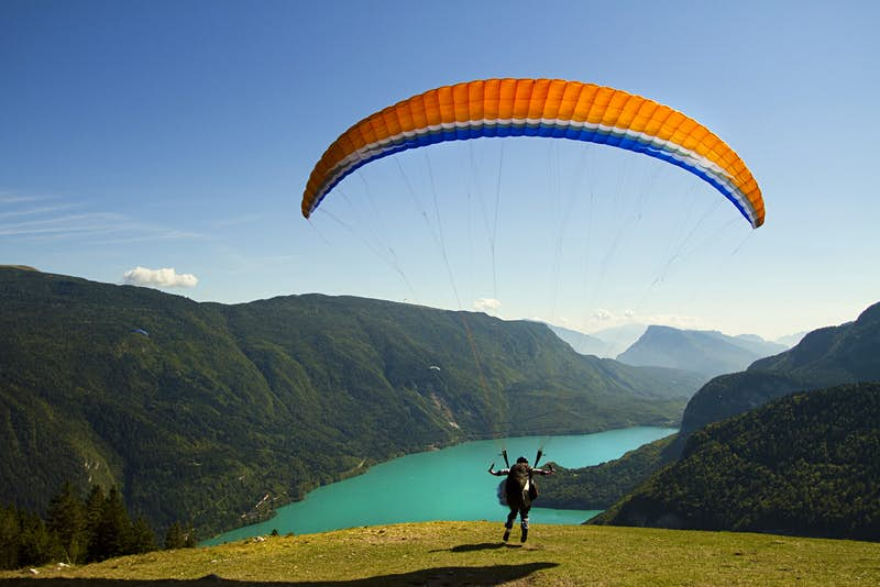 A paraglider takes off over the turquoise waters of Lake Molveno