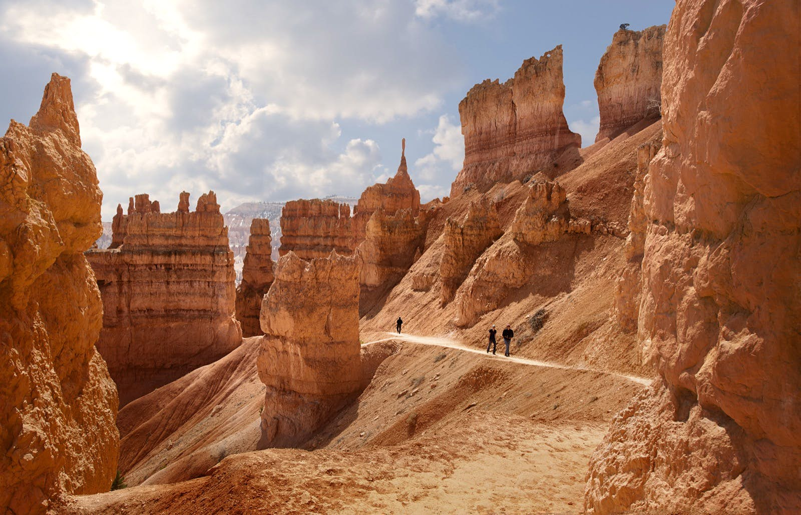 A few people walk in opposite directions through monumental rock formations in the red desert in Bryce Canyon, Utah.