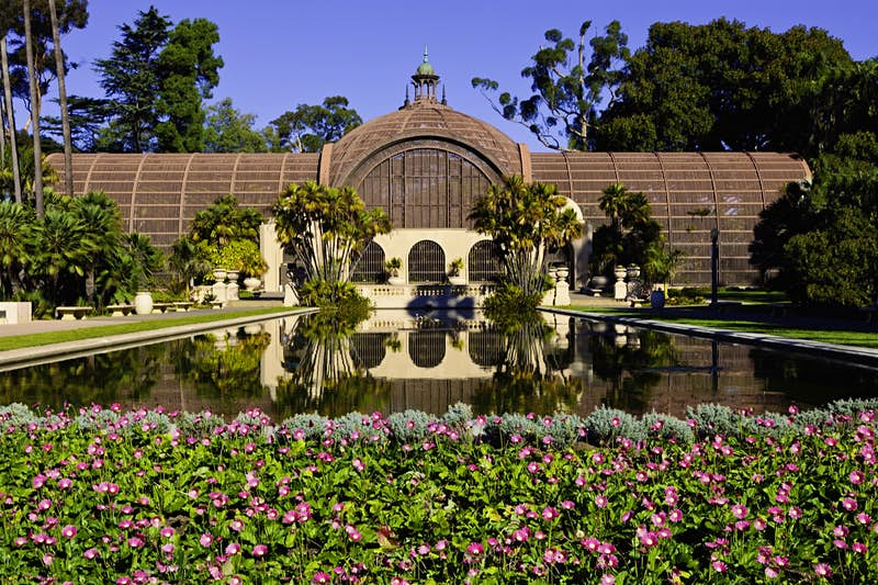 A domed building in lath is mirrored in the lily pond stretching out in front a great sight on a perfect weekend in San Diego