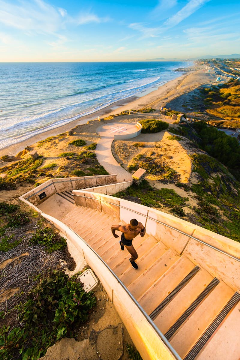 a man runs up a flight of stairs from the beach in the sun on a perfect weekend in San Diego