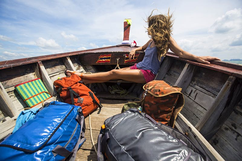 A woman sits in the bow of a boat with backpacks; she is looking away from the camera and her hair is blowing around