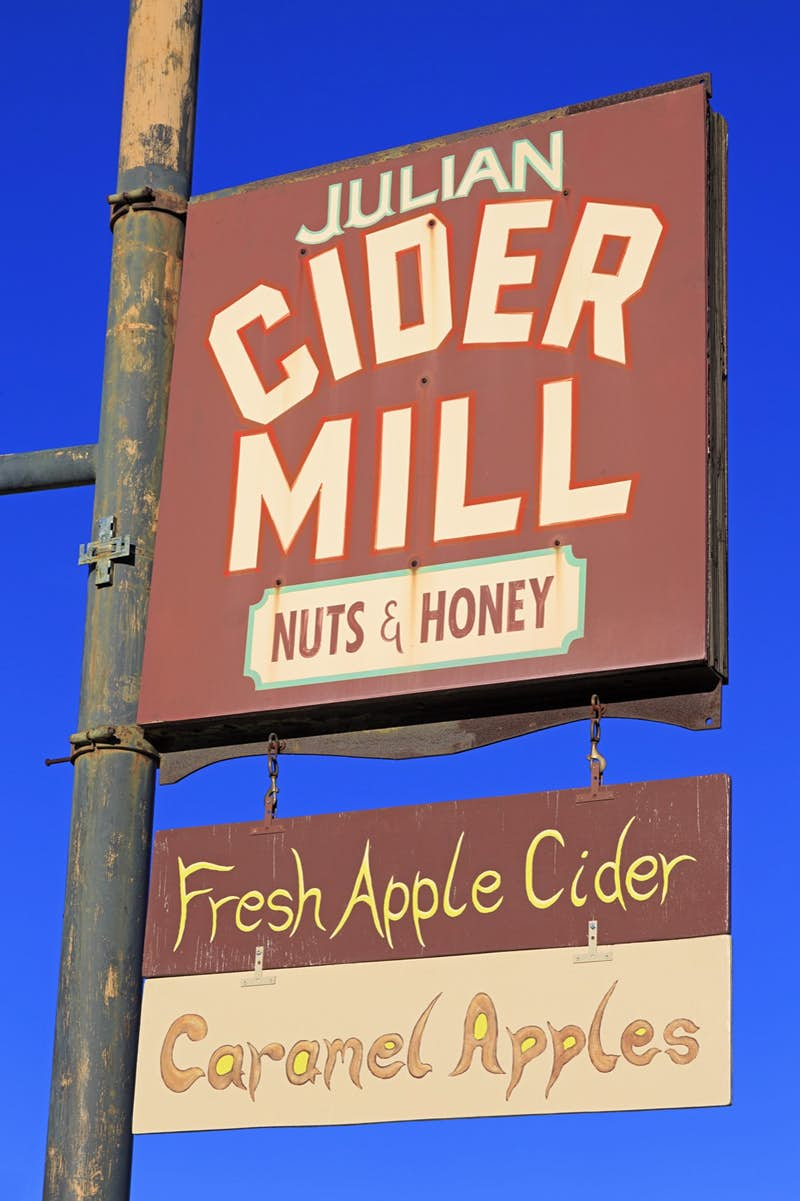 A sign that says Julian Cider Mill in large font and Nuts & Honey in smaller font another sign below says Fresh Apple Cider followed by Caramel Apples against a bright blue sky