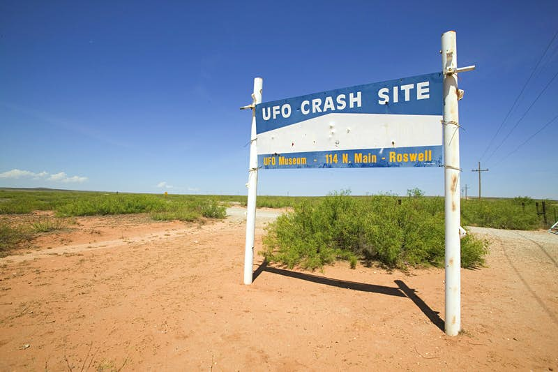 A sign that says 'UFO Crash Site' stands to the side of a dusty track