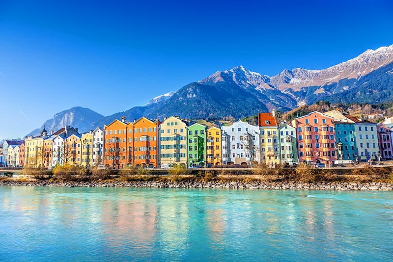 The colourful houses of Innsbruck sit on the river Inn, with the snow-capped Nordkette mountains rising behind