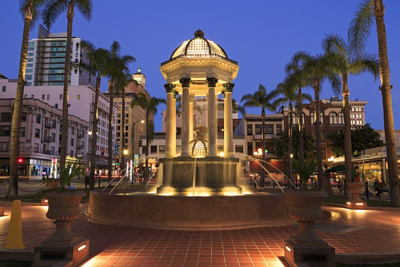 Broadway fountain in the Horton Plaza Park is a fountain surrounded by palm trees and buildings on a perfect weekend in San Diego