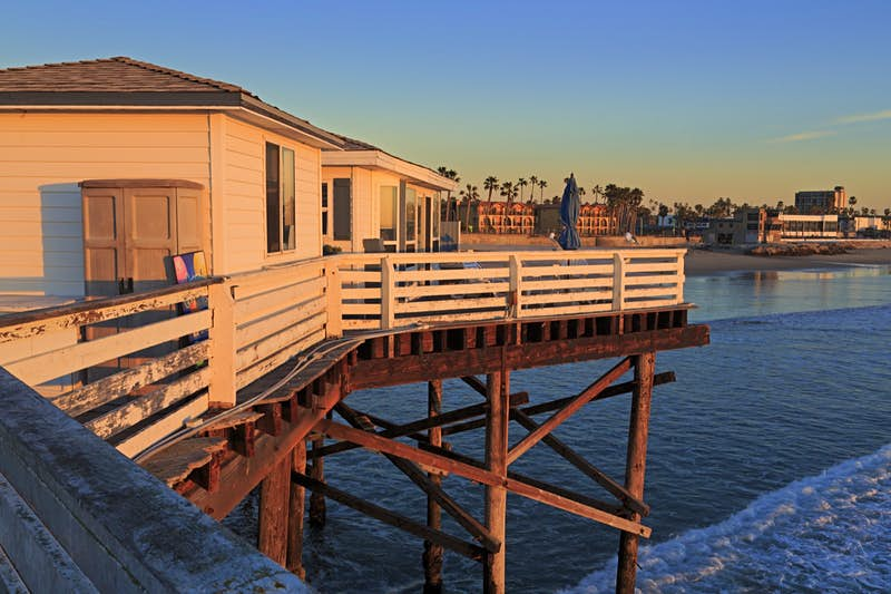 Two white cottages are built on a pier over the Pacific Ocean stay here on a perfect weekend in San Diego