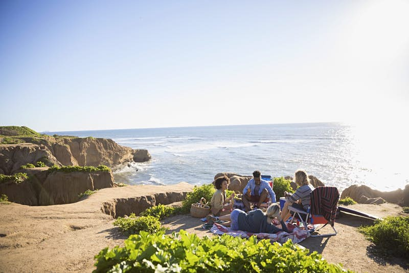 Five people sit on colorful blankets with food on a cliff overlooking the ocean