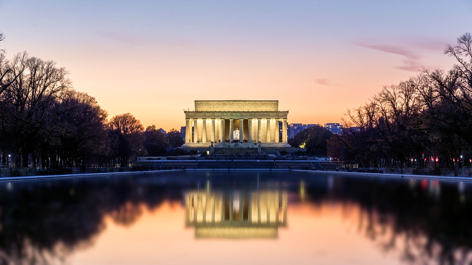 The Lincoln Memorial lit up at night reflected in the pond below. A trip to Washington isn't complete without a selection from the audiobooks for US road trips.