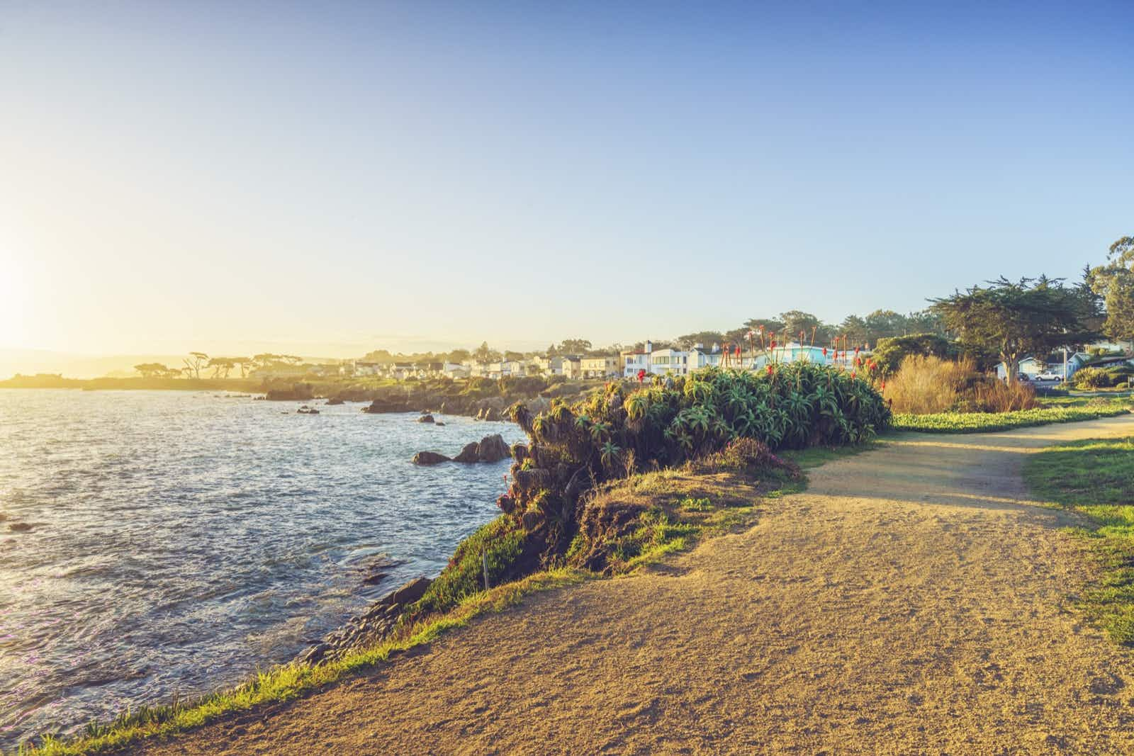 a sandy path leads past a rocky shoreline lined with wild fauna with stately homes in the background in Monterey, California