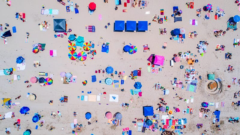 Colorful umbrellas and towels decorating a beach in San Diego are seen from above