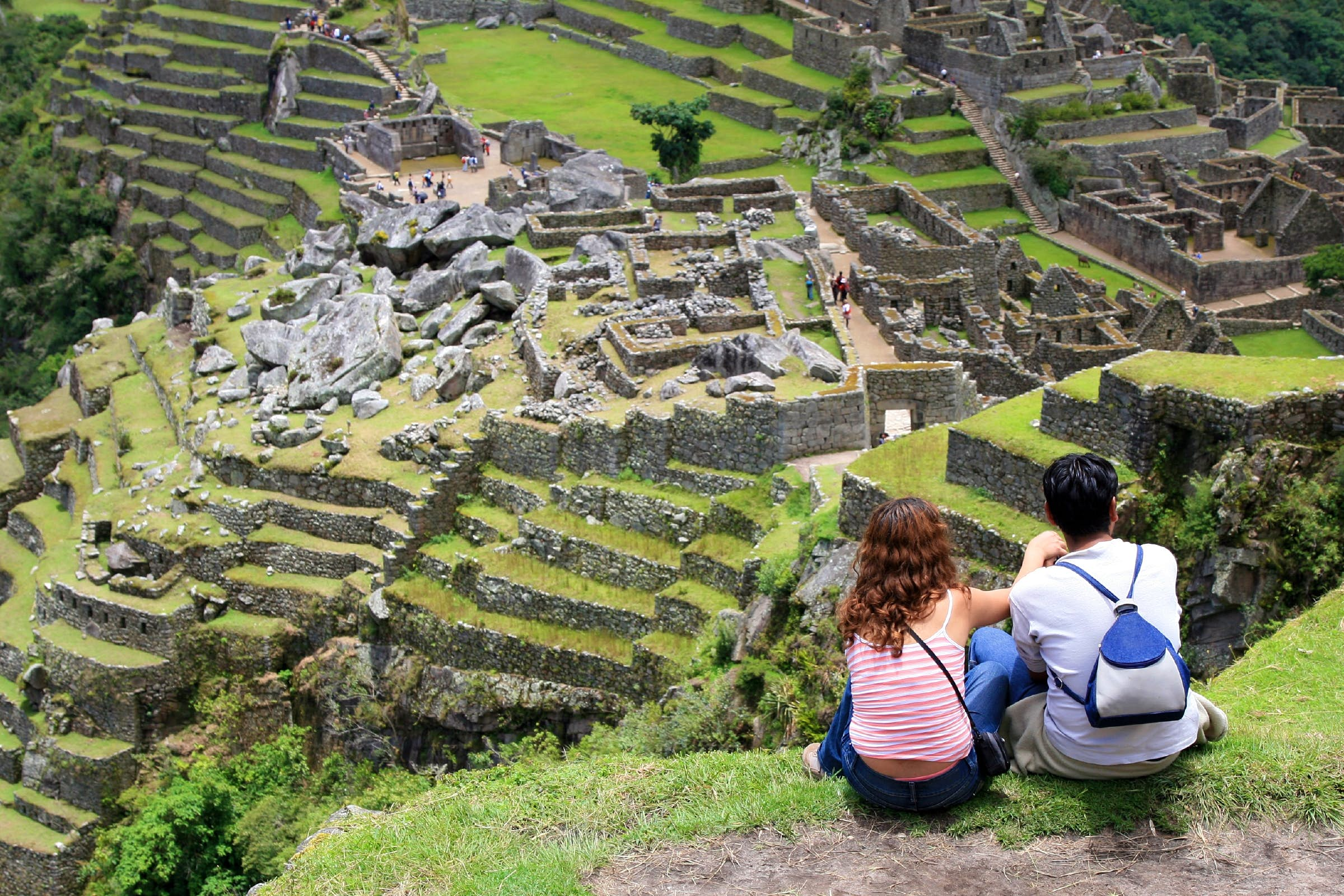 Young couple sitting together on a hill top overlooking Machu Picchu