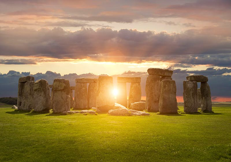 The sun at sunset aligns with standing sarsen stones of Stonehenge against a cloudy grey sky. Could this ancient structure be a UFO signal?
