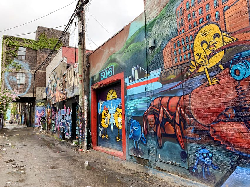 Vibrantly colored street art is seen all over the walls of an alleyway