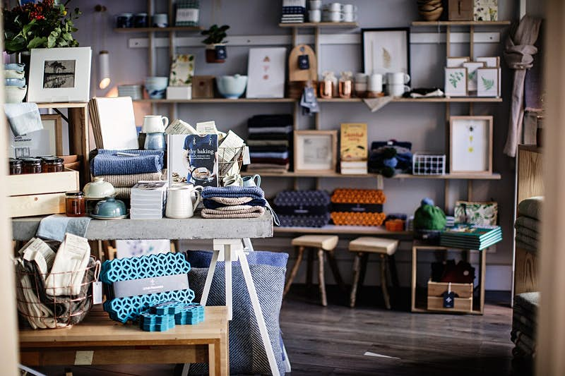 Dublin independent shops - the interior of the Irish Design Shop which is bursting with homewares, stools, woolly blankets and books piled on tables and shelves against the dark grey walls